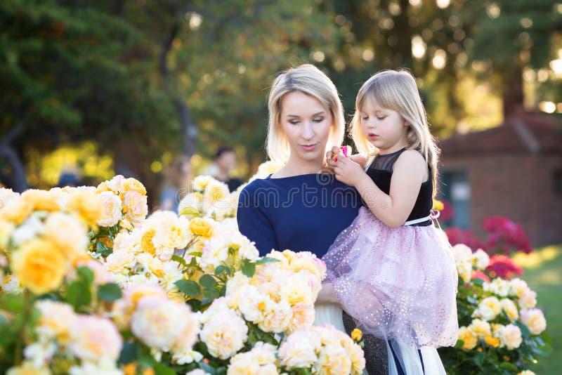 Caucasian kvinna med lilla flickan i h?nder i rosa tr?dg?rd, mamma och mig begrepp, kel som till varandra ser royaltyfria foton