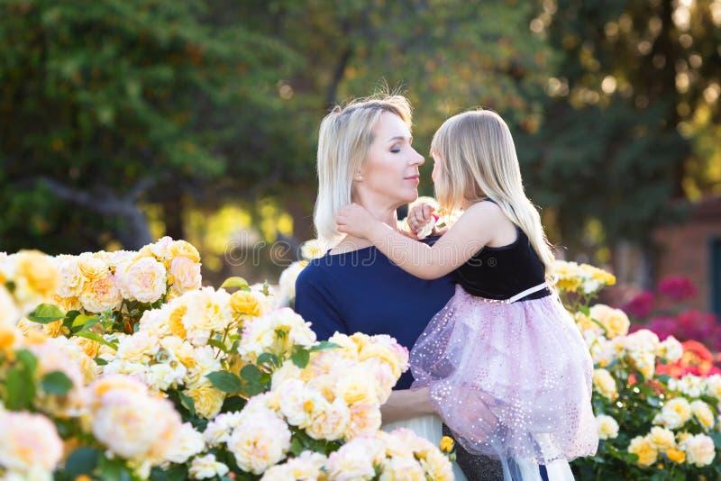 Caucasian kvinna med lilla flickan i h?nder i rosa tr?dg?rd, mamma och mig begrepp, kel som till varandra ser royaltyfri bild