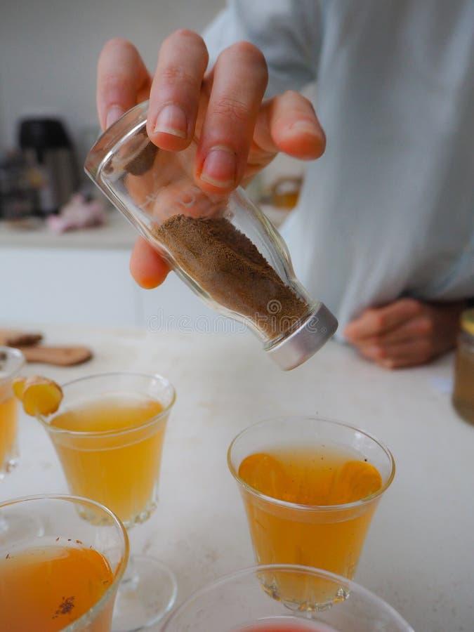 Caucasian kvinna som häller kanelbruna kryddor på ett exponeringsglas med nytt och hemlagat kombuchate fotografering för bildbyråer