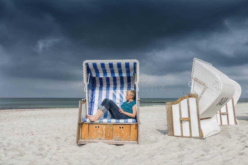 Caucasian kvinna som kopplar av i strandkorb på det baltiska havet fotografering för bildbyråer