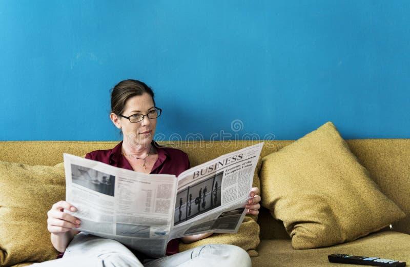Caucasian kvinna som läser tidningen royaltyfri foto