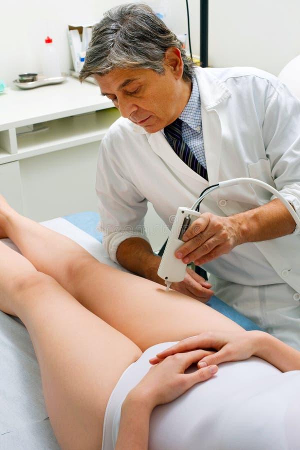 Caucasian kvinna som mottar laser-behandling på benet från en man royaltyfri fotografi