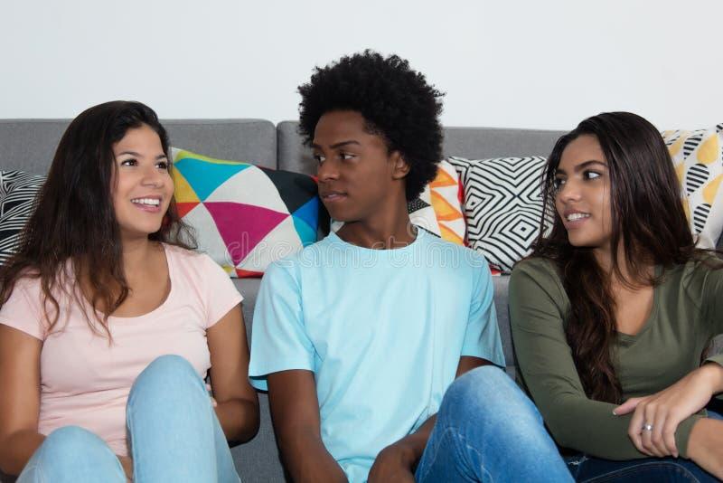 Caucasian kvinna som talar med amerikanska och afrikanska vänner för latin - arkivfoton