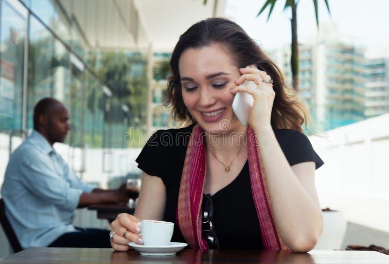 Caucasian kvinna som talar på telefonen och dricker kaffe i en kafeteria royaltyfria bilder