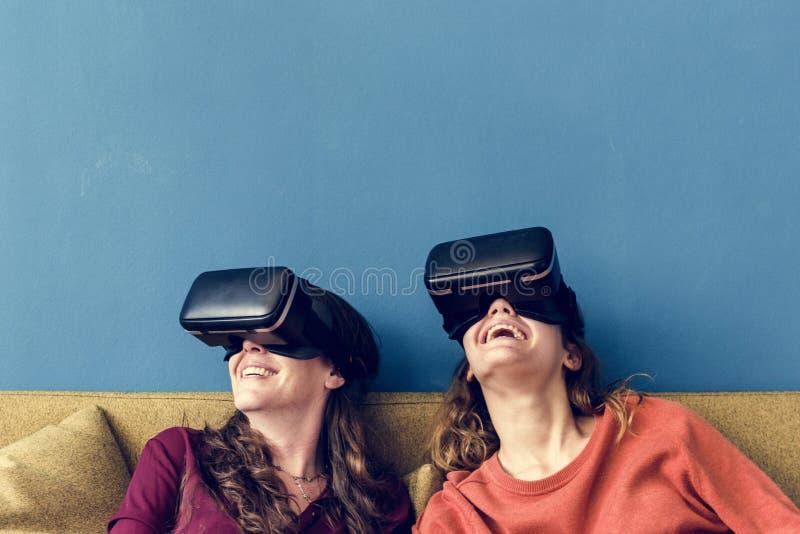 Caucasian kvinna som två använder VR på en soffa arkivfoton