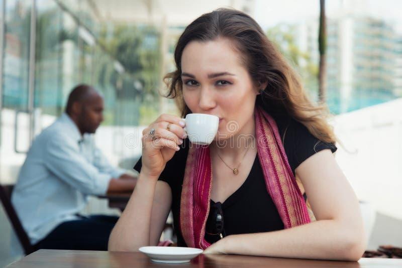 Caucasian kvinna som tycker om en kopp kaffe i en restaurang arkivbild