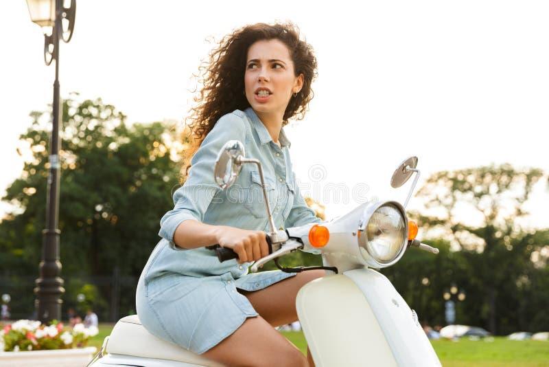 Caucasian kvinna20-tal som rider på den stilfulla mopeden till och med stadsgatan arkivbild