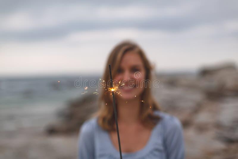 Caucasian kvinnaanseende med gnistrandet på stranden arkivbild
