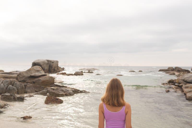Caucasian kvinnaanseende på stranden arkivbild