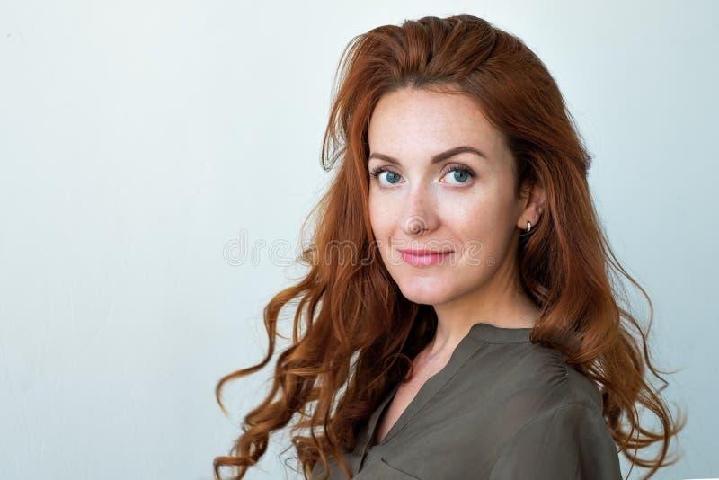 Caucasian kvinnamodell med ljust rödbrun hår som inomhus poserar arkivbild