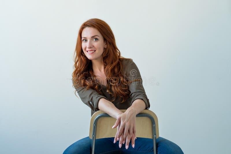 Caucasian kvinnamodell med ljust rödbrun hår som inomhus poserar arkivfoton