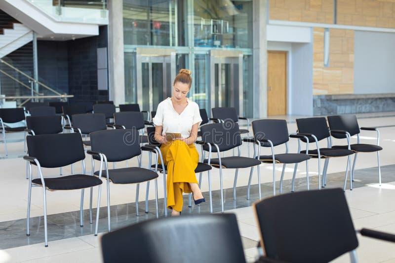 Caucasian kvinnlig ledare som ser den digitala minnestavlan, medan sitta på stol i tomt konferensrum arkivbild