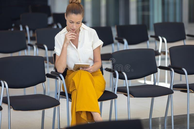 Caucasian kvinnlig ledare som ser den digitala minnestavlan, medan sitta på stol i tomt konferensrum fotografering för bildbyråer