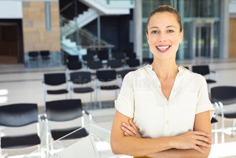 Caucasian kvinnlig ledare som ser kameran, medan stå i tomt konferensrum arkivfoto