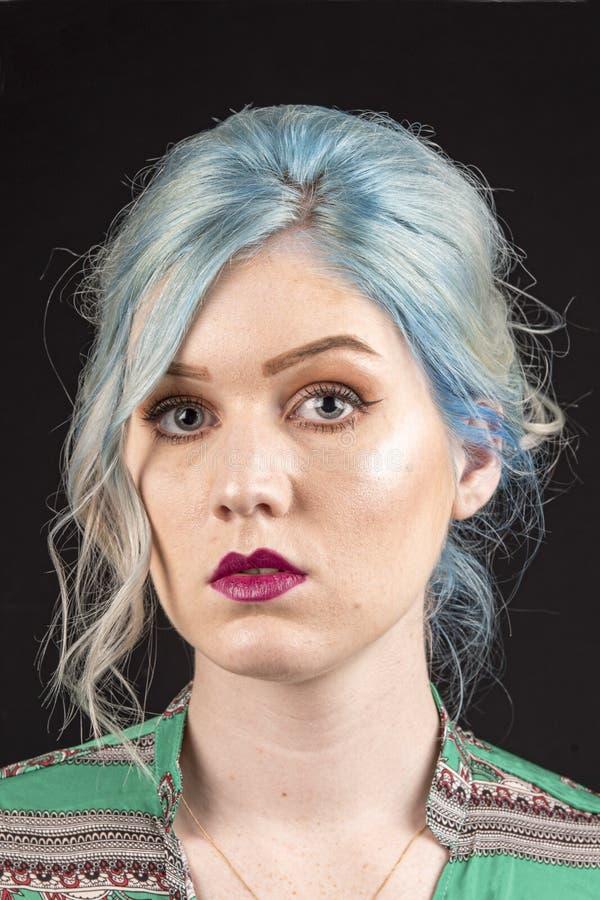 Caucasian kvinnlig modell, ålder 22, blått färgat hår, röd grön och röd skjorta för kanter, Isolerat på svart bakgrund Övretorso  arkivfoton