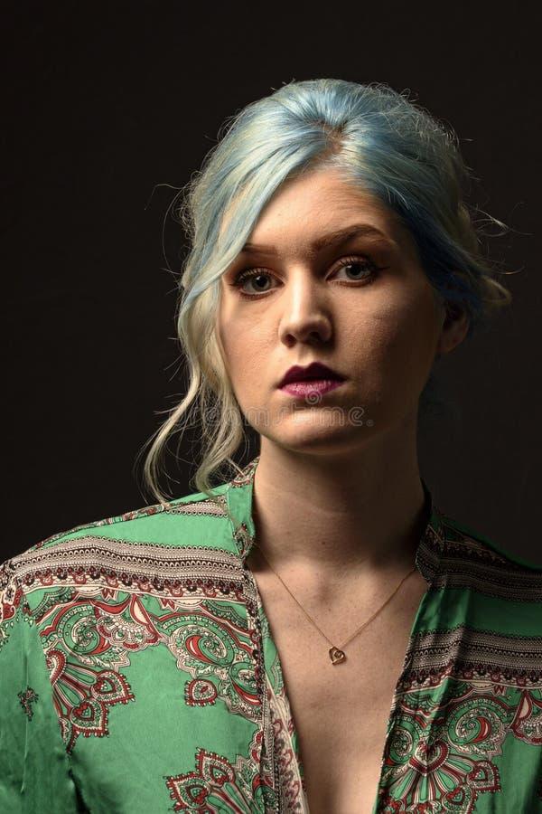 Caucasian kvinnlig modell, ålder 22, blått färgat hår, röd grön och röd skjorta för kanter, Isolerat på svart bakgrund head skuld arkivfoton