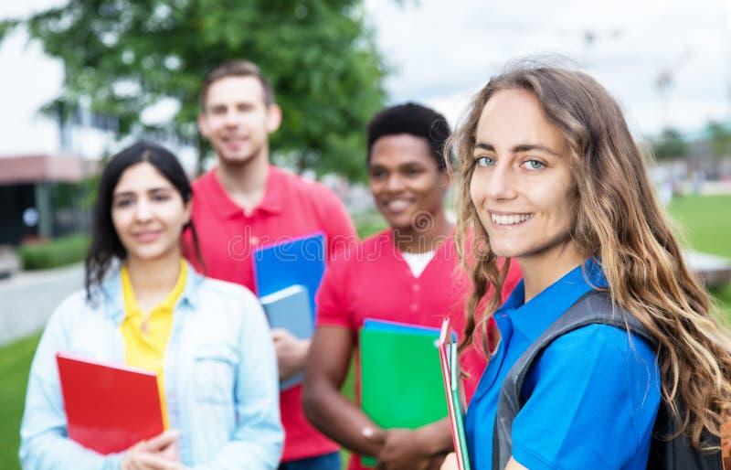 Caucasian kvinnlig student med gruppen av multietniska studenter royaltyfri foto