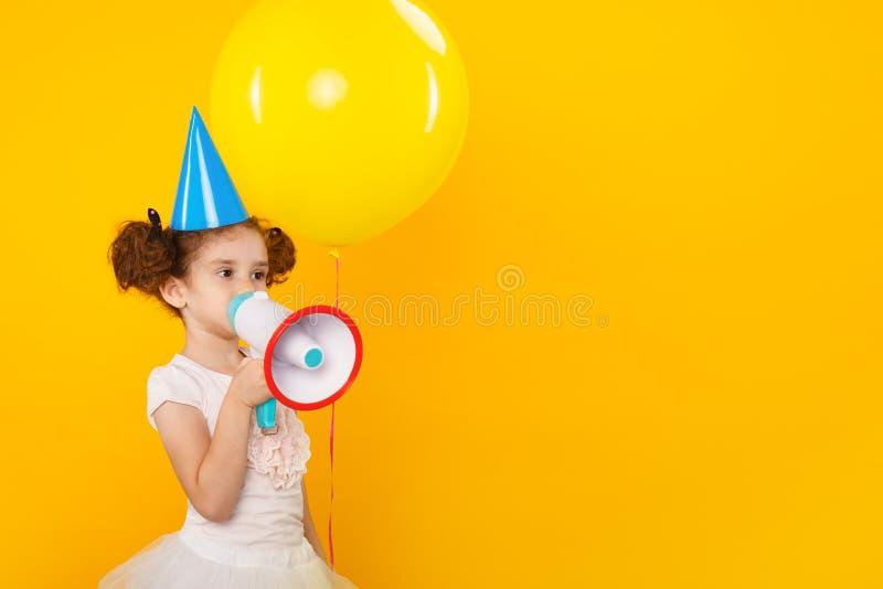 Caucasian liten flicka att meddela vid megafonen som isoleras på gul bakgrund med kopieringsutrymme svart telefon f?r kommunikati royaltyfri bild