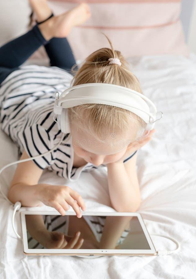 Caucasian liten flicka i hållande ögonen på minnestavla för Headphone i säng royaltyfri foto