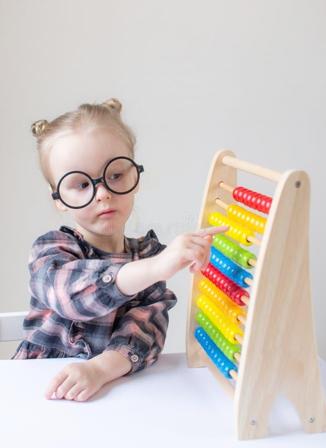 Caucasian liten flicka med runda exponeringsglas Liten lärare arkivfoton