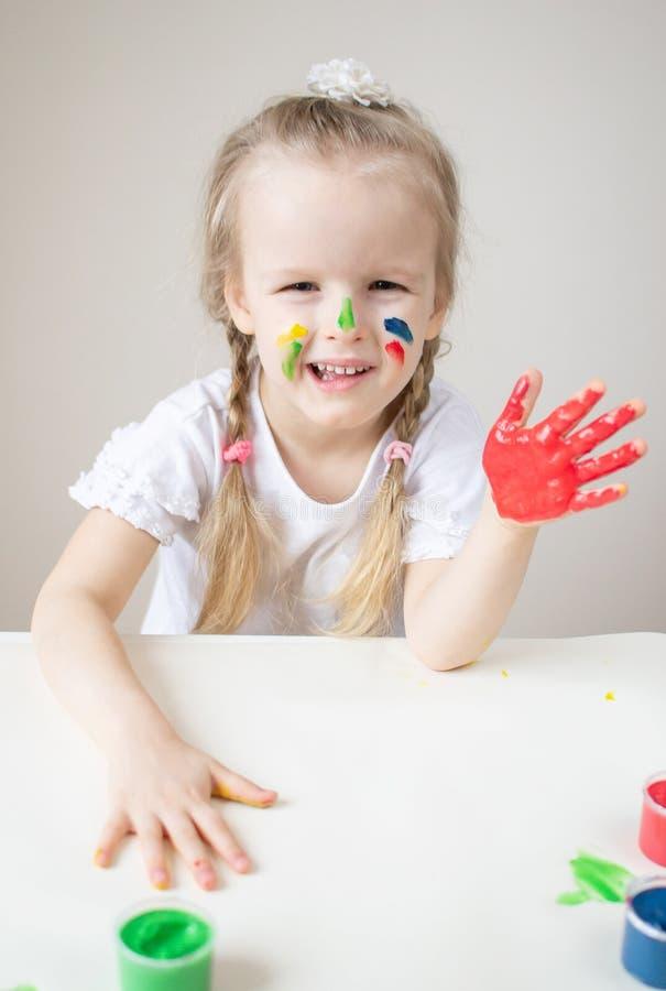 Caucasian liten flickamålning med färgrika händer målar hemmastadd tidig utbildning arkivfoto