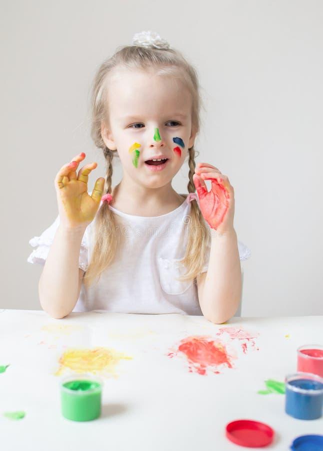 Caucasian liten flickamålning med färgrika händer målar hemmastadd tidig utbildning arkivbilder