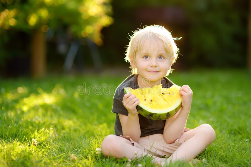 Caucasian little boy with blond hairs eating yellow watermelon on backyard. Seasonal fruits and vegetables for kids royalty free stock images