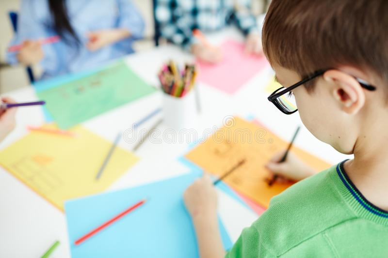 Schoolboy on art class. Caucasian little boy in glasses sitting at school desk and drawing on colored paper on blurred background stock photo
