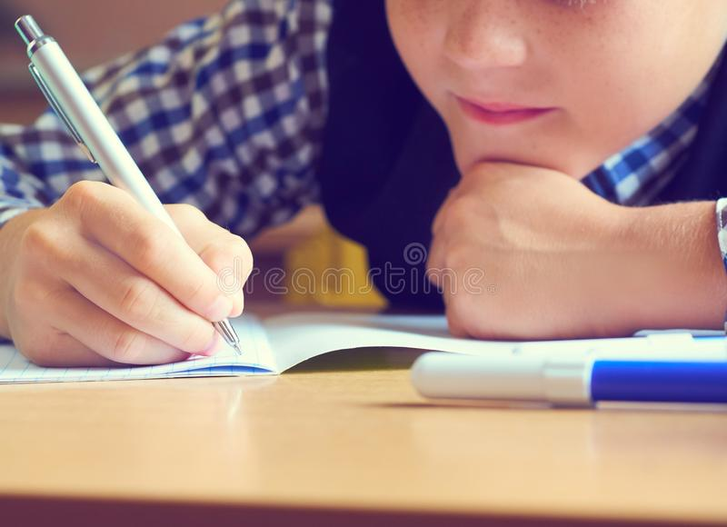 Caucasian little boy holding pen and writing in notebook. Close up. Selective focus stock photography