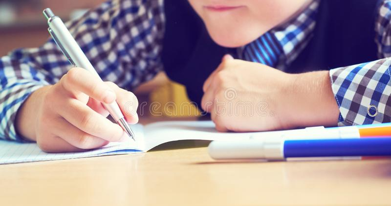 Caucasian little boy holding pen and writing in notebook. Close up. Selective focus stock image