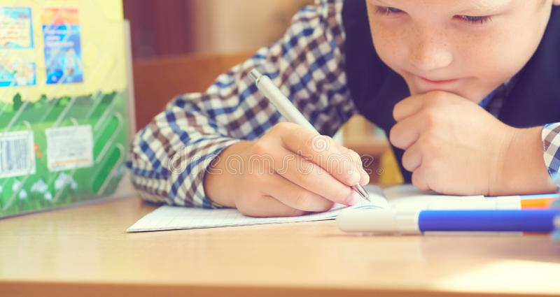 Caucasian little boy holding pen and writing in notebook. Close up. Selective focus royalty free stock photography