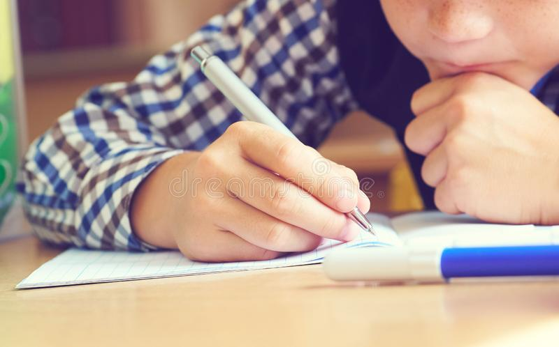 Caucasian little boy holding pen and writing in notebook. Close up. Selective focus royalty free stock photo