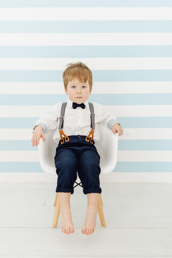Caucasian Little Boy Sitting Straight on Chair. Peaceful Toddler Seat Calmly on Striped Wall Background. Handsome Quiet Preschooler Child Male Kid Model stock images