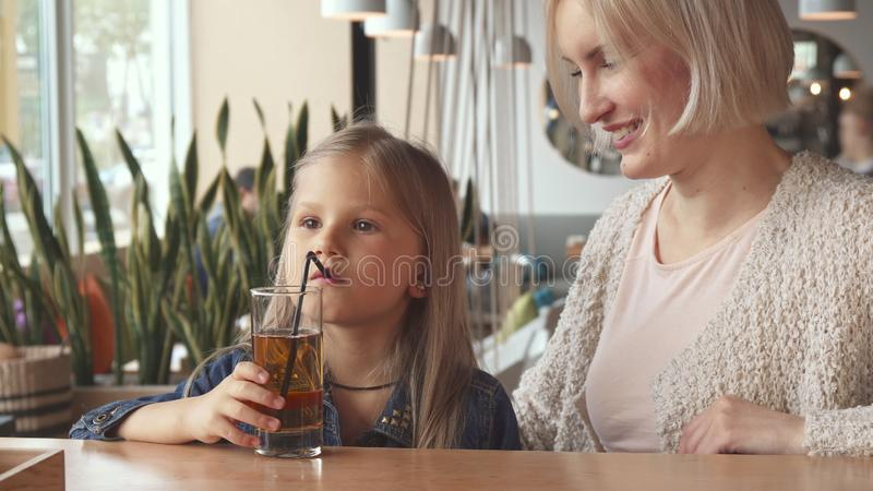 Little girl drink some beverage through a straw at the cafe royalty free stock photography