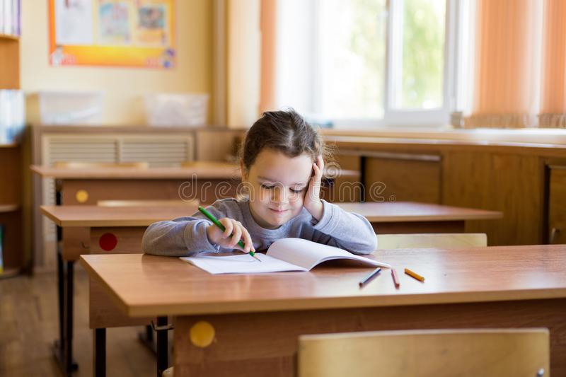 Caucasian little girl sitting at desk in class room and begins to carefully draw in a pure notebook. Happy pupil.  royalty free stock images