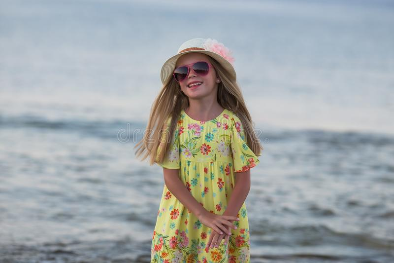 Caucasian little girl smiling happy on sunny summer or spring day outside in park by lake. Pretty girl. Summer girl portrait. Caucasian little girl smiling happy stock photography