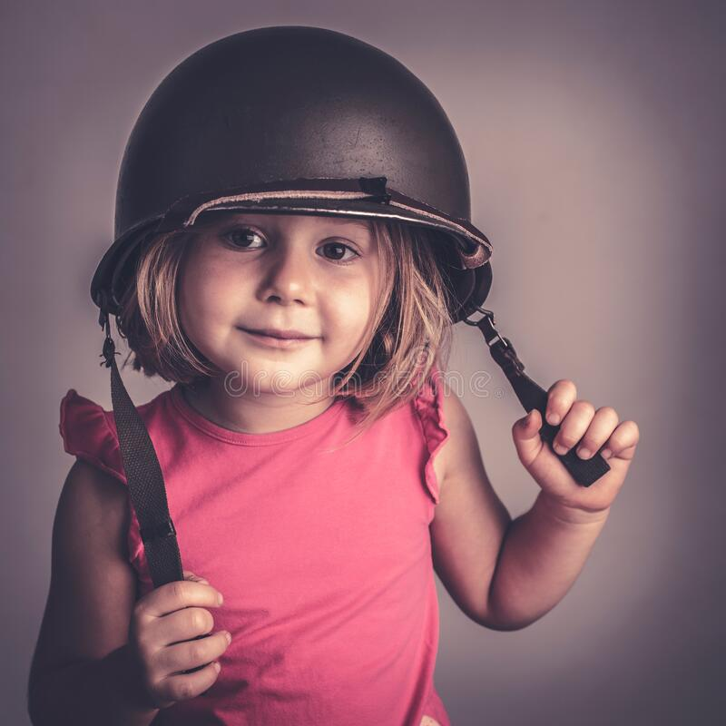 Caucasian little girl wearing a military helmet royalty free stock photo