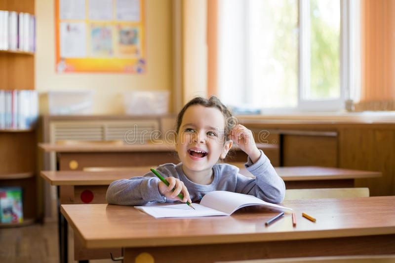 Caucasian little smiling girl sitting at desk in class room and begins to carefully draw in a pure notebook. Happy pupil.  royalty free stock photography