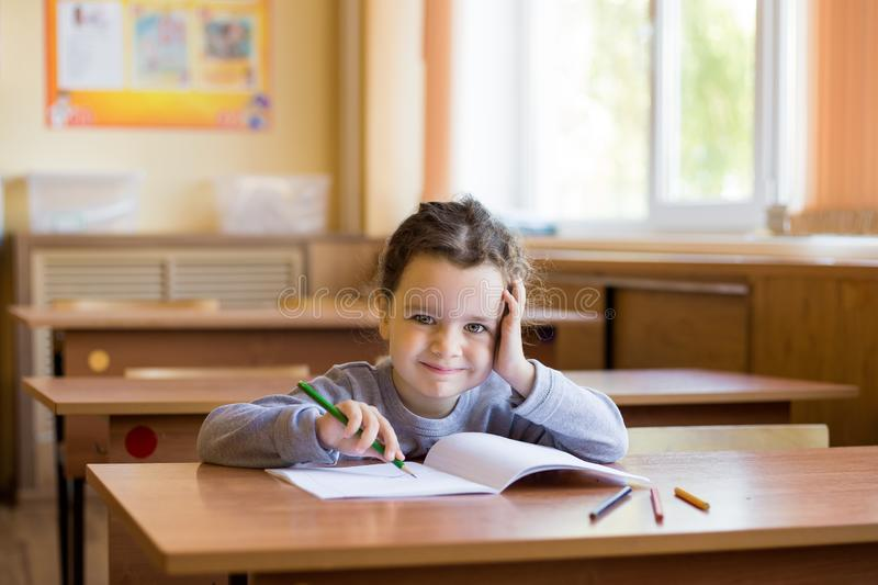 Caucasian little smiling girl sitting at desk in class room and begins to draw in a pure notebook.  royalty free stock photo