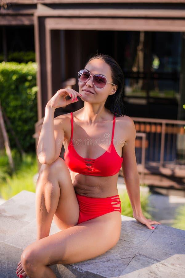 caucasian lounger för asiatisk härlig bikini som ligger nära barn för kvinna för lopp för sun för pölsemesterort le solbada tropi arkivfoton