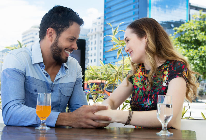 Caucasian love couple holding hands in a restaurant outdoor in the summer stock photos