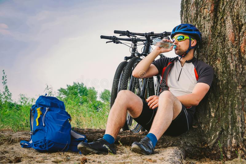 Caucasian male cyclist active lifestyle resting under tree after exercising bicycle drinking water from bottle. Sportsman in. Helmet and sportswear. Hand flask stock photos
