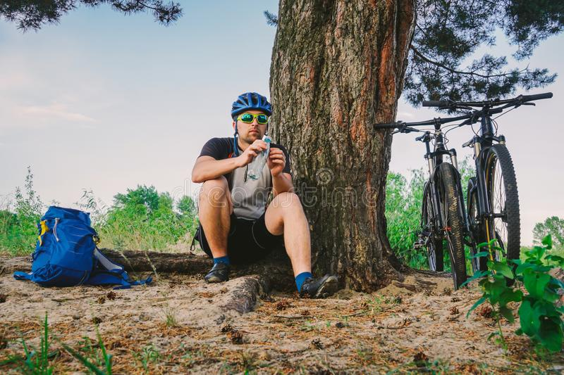 Caucasian male cyclist active lifestyle resting under tree after exercising bicycle drinking water from bottle. Sportsman in. Helmet and sportswear. Hand flask stock image