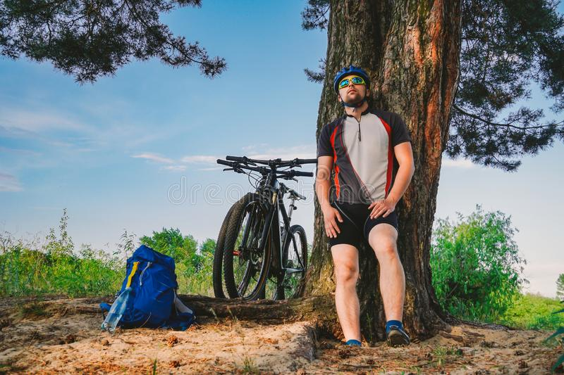 Caucasian male cyclist active lifestyle resting under tree after exercising bicycle drinking water from bottle. Sportsman in. Helmet and sportswear. Hand flask stock photo