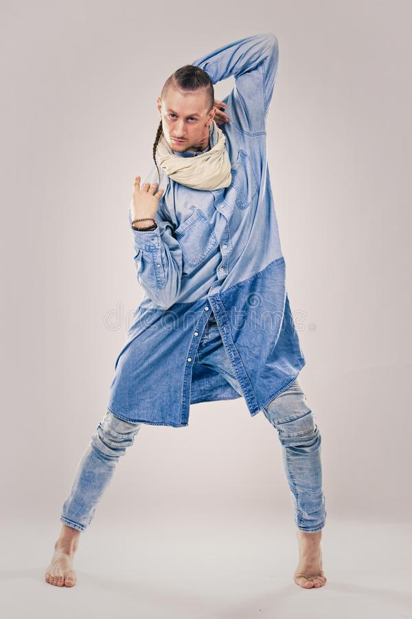 Male contemporary hip hop dancer in denim. Caucasian male dancer wearing blue denim shirt and pants on light background performing hip hop and contemporary style royalty free stock images