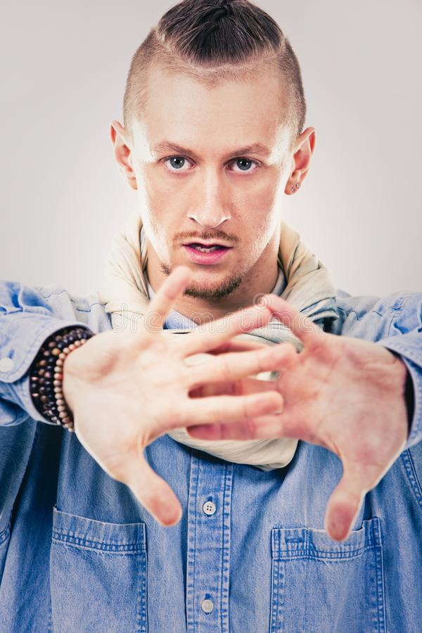 Male contemporary hip hop dancer in denim. Caucasian male dancer wearing blue denim shirt and pants on light background performing hip hop and contemporary style royalty free stock photos