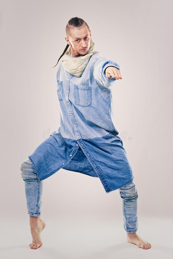 Male contemporary hip hop dancer in denim. Caucasian male dancer wearing blue denim shirt and pants on light background performing hip hop and contemporary style stock image