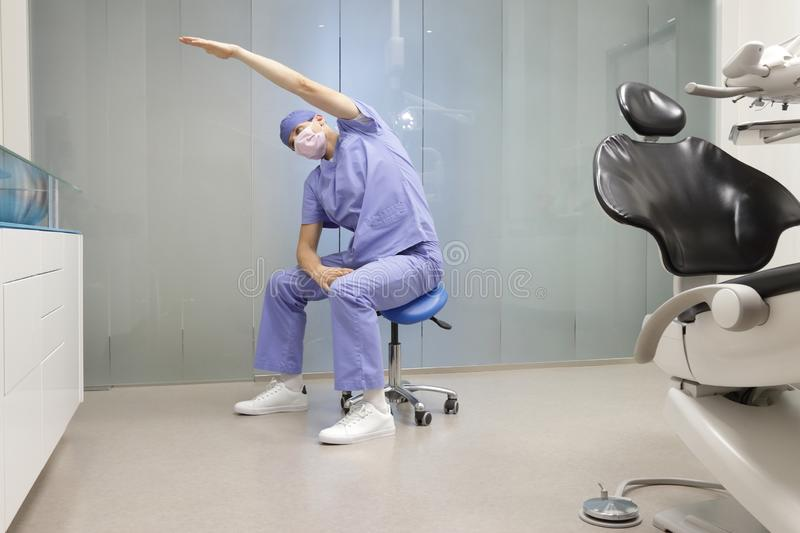 Dentist on mobile dental saddle stretching arm and back stock photography