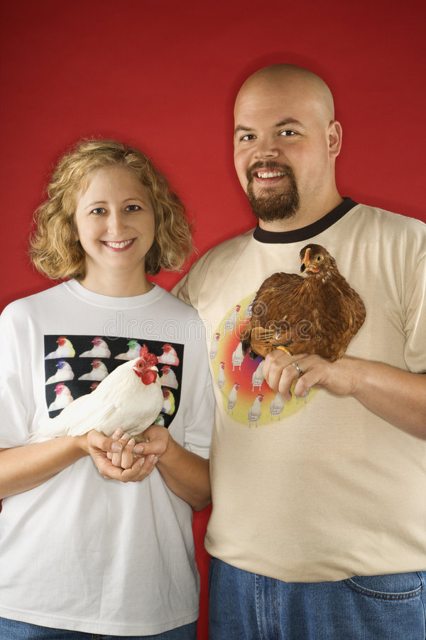 Caucasian male and female holding chickens. stock photography