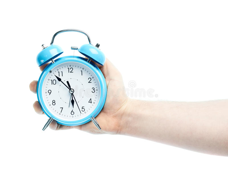 Caucasian male hand holding alarm clock royalty free stock photography